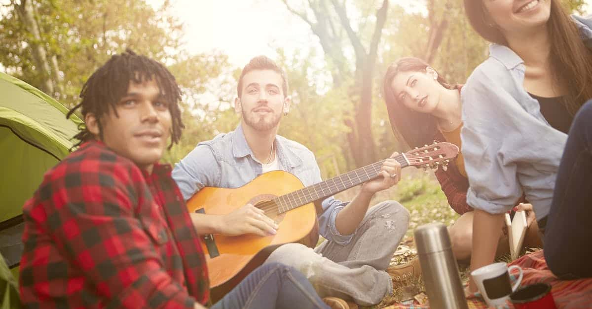 A group of people sitting at a guitar