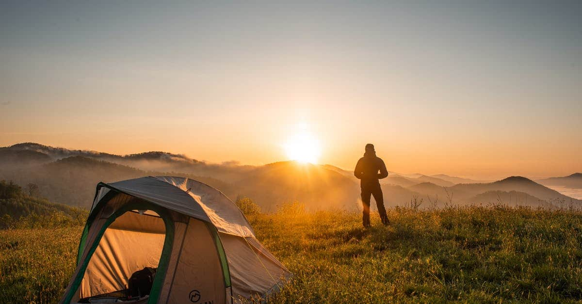 A man standing in front of a sunset over a tent