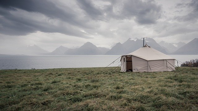 A tent in a field with a mountain in the background