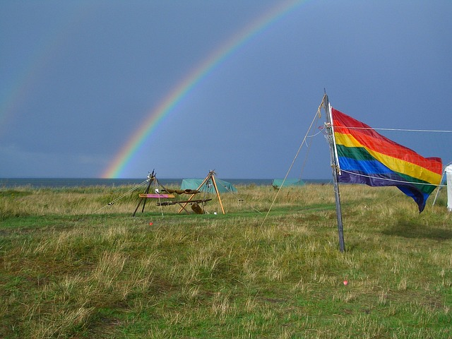 A rainbow over a field flying a kite