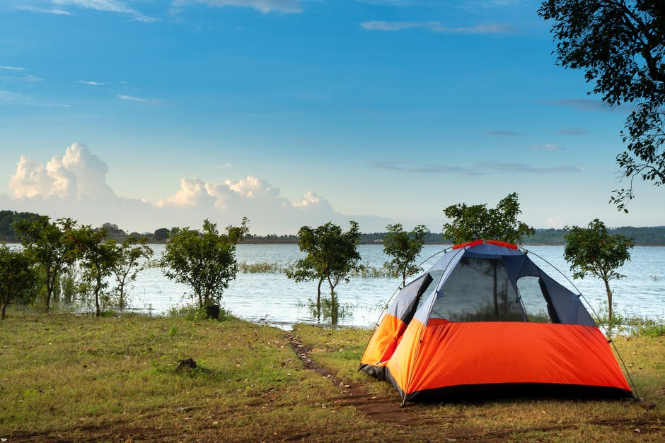 A tent in a field next to a body of water