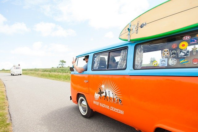 An orange bus is parked on the side of a road
